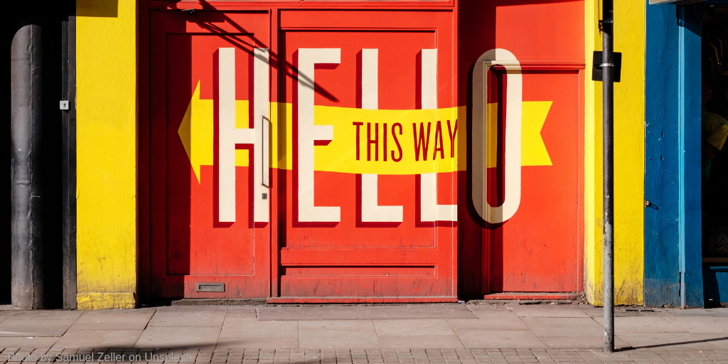 photo of a painted door that says Hello this way